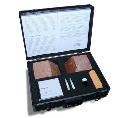 Institutionalized Art, multiple; suitcase contains a brick cut into 2 parts, video, instruction text, special glue, cloths for cleaning glass; mixed media, 2005